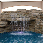 Beautiful waterfalls cascading into a pool -- Custom Pools in Lakeland
